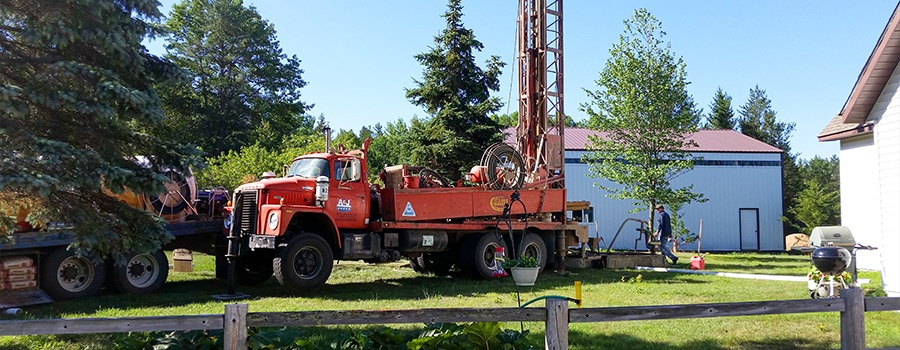 red A& J Well Drilling rig working in a yard